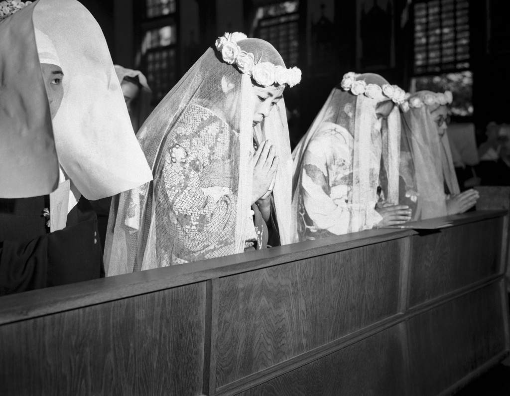 The girls offer up prayers a few minutes before they took their first vow in their first step towards sisterhood, they are at the altar in Tokyo, Japan on Oct. 8, 1946. (AP Photo/C. P. Gorry) Ref #: PA.10807577