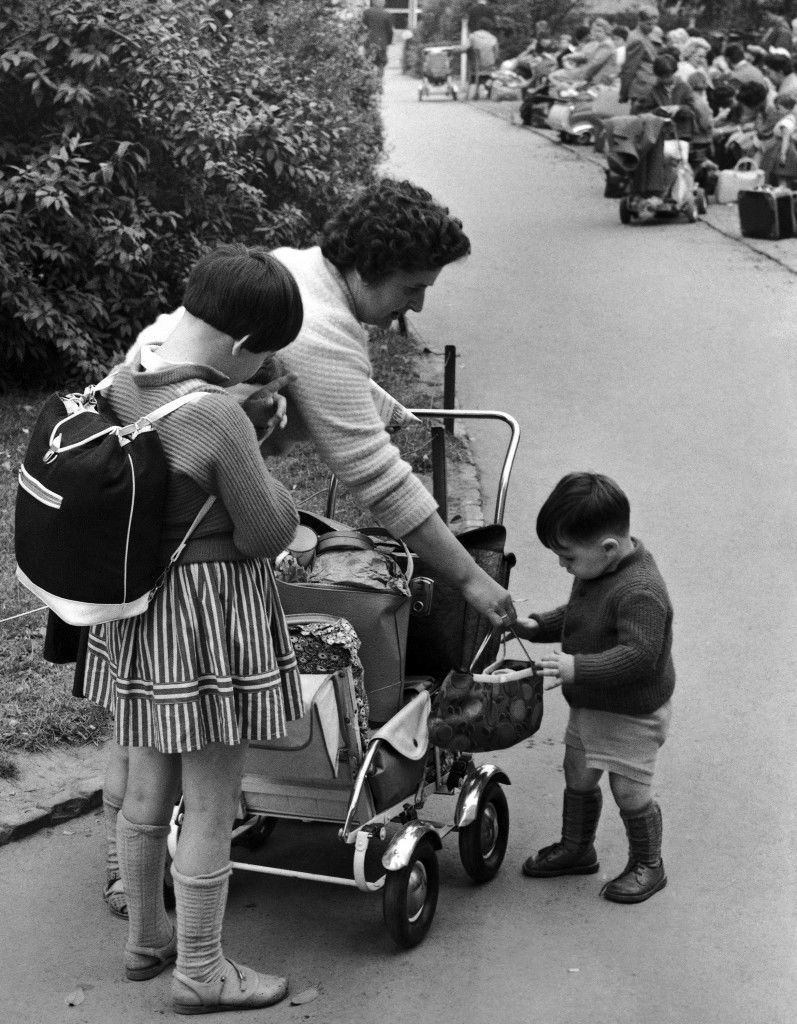 A mother and her two children, refugees from communist East Germany, wait at the Marienfelde Receiving Camp in West Berlin, Germany on August 2, 1961, as the husband completed registration formalities at the administration office. More than a 1,000 refugees are pouring into West Berlin every day. (AP Photo) Ref #: PA.10810047  Date: 02/08/1961