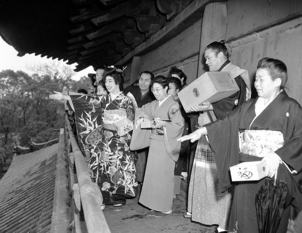 "The change of season, or ""Setsubun,"" is celebrated in traditional fashion at the Asakusa Temple in Tokyo on Feb. 9, 1950 as a geisha girl, a sumo wrestler and other prominent personalities throw out roasted beans to the crowd that has gathered. As the beans are scattered, the person who tosses chants or sings: ""Devil outside, good luck inside."" Custom is part of the temple festivities and Merry-making which greet the change of season, which comes on February 3 in Japan. To be chosen as one of the bean-throwers at the annual temple rites is considered a great honor, for which geishas, wrestlers, movie actresses and other public figures vie. (AP Photo/Charles Gorry) Ref #: PA.10887844"