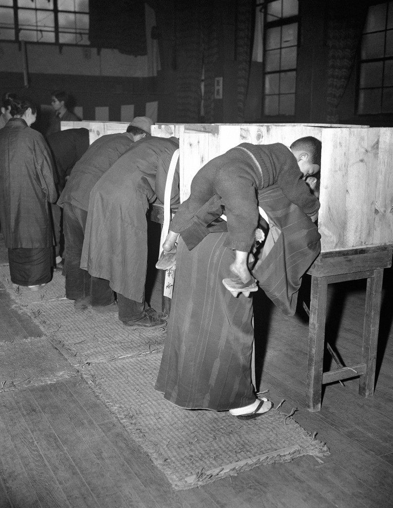 A Japanese woman carries her son on her back as she marks her ballot in Tokyo on April 10, 1946, in Japan's first free election in generations. Japanese women exercised the right to vote for the first time to help elect a new lower house in the diet. (AP Photo/CPG) Ref #: PA.10974430