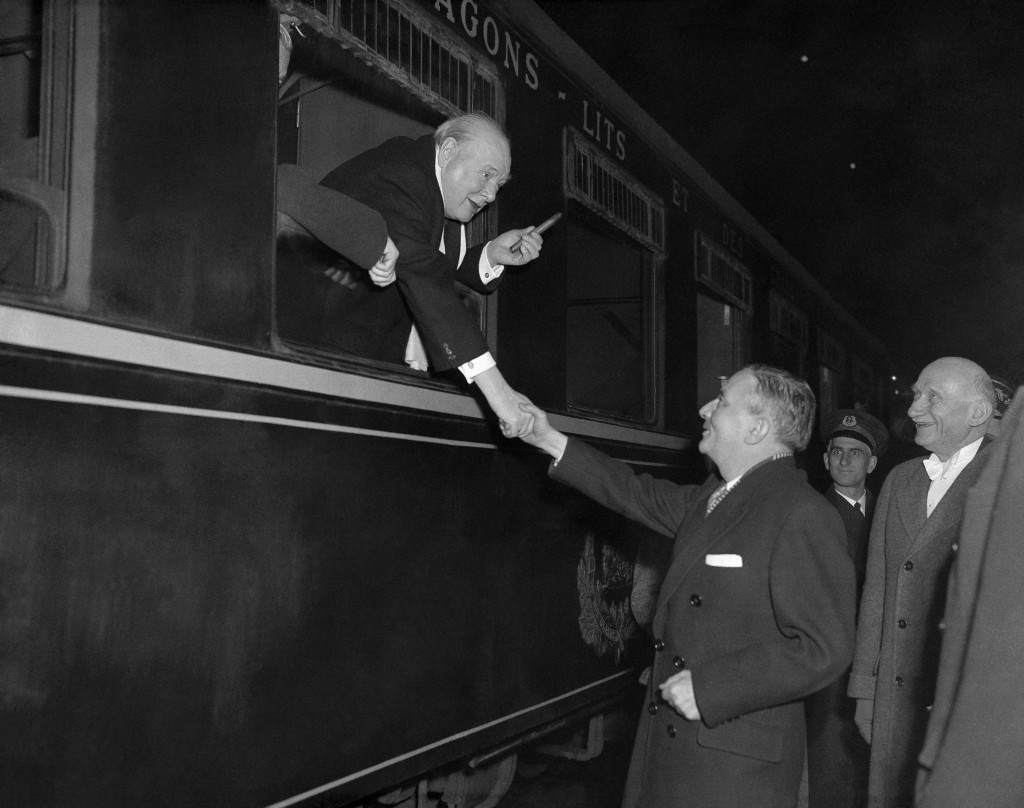 Britain's Prime Minister Winston Churchill, holding familiar cigar, leans from a train window at Gare du Nord, Paris, France on Dec. 18, 1951, to big goodbye, to French Defense Minister Georges Bidault and Foreign Minister Robert Schuman. Churchill was leaving the French capital after conferences with other West European leaders. (AP Photo) Ref #: PA.11070179  Date: 18/12/1951