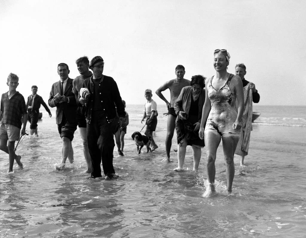 Florence Chadwick, 32, year old San Diego, California, swimmer, lands at Sangattes on the French coast at 2.40 pm on September 11, 1951 thus becoming the first woman to swim the English channel both ways. She swam from St. Margaret's bay, Dover, leaving there at 10.30 p.m., on September 10. In 1950 Miss Chadwick swam from France to England. Her time for the England France crossing was 16 hours 22 minutes. Only a handful of people and children are present to greet Miss Chadwick as she walks ashore at Sangattes beach, midway between Calais and Cap Gris Nez on the French coast in France on Sept. 11, 1951. (AP Photo/Jim Pringle) Ref #: PA.11141813