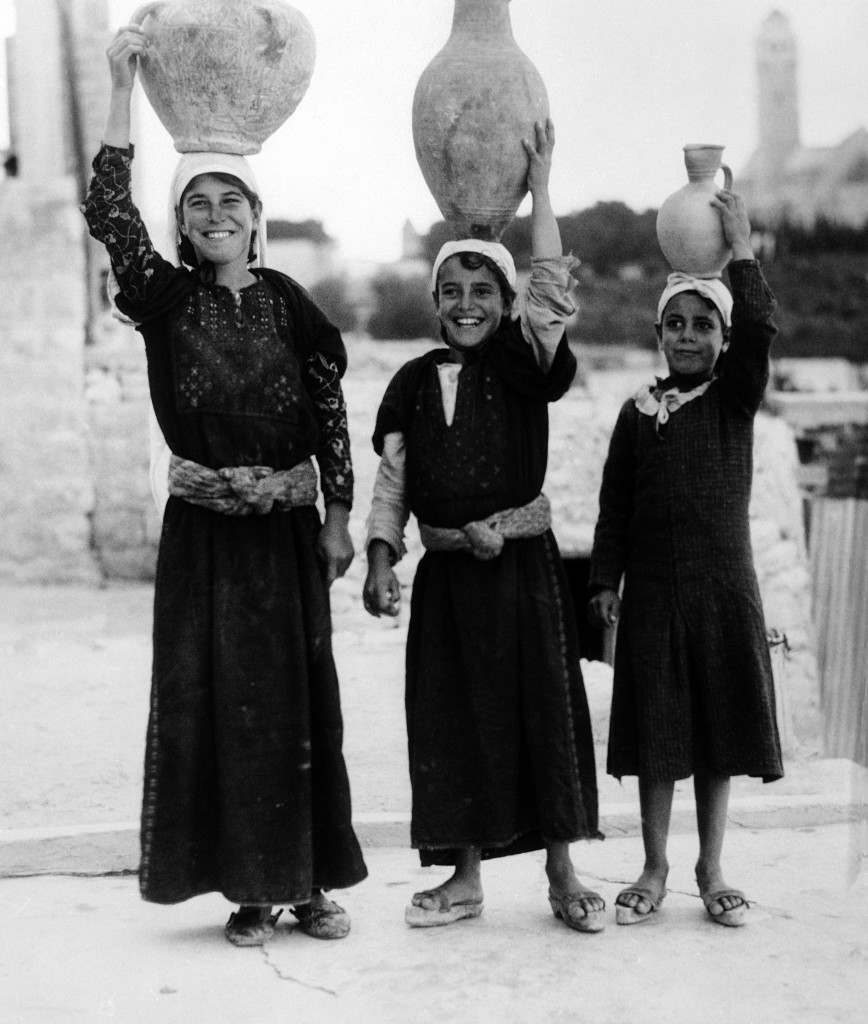 Typical group of women of the holy land who, as in the time of the old testament, carry water from the wells on their heads in quaint, home-made vessels of clay. They dress, too, much in the same way as the women did in the time of Christ. This group on the Mount of Olives, in Jerusalem, on Sept. 1, 1938. (AP Photo) Ref #: PA.11202016 Date: 01/09/1938