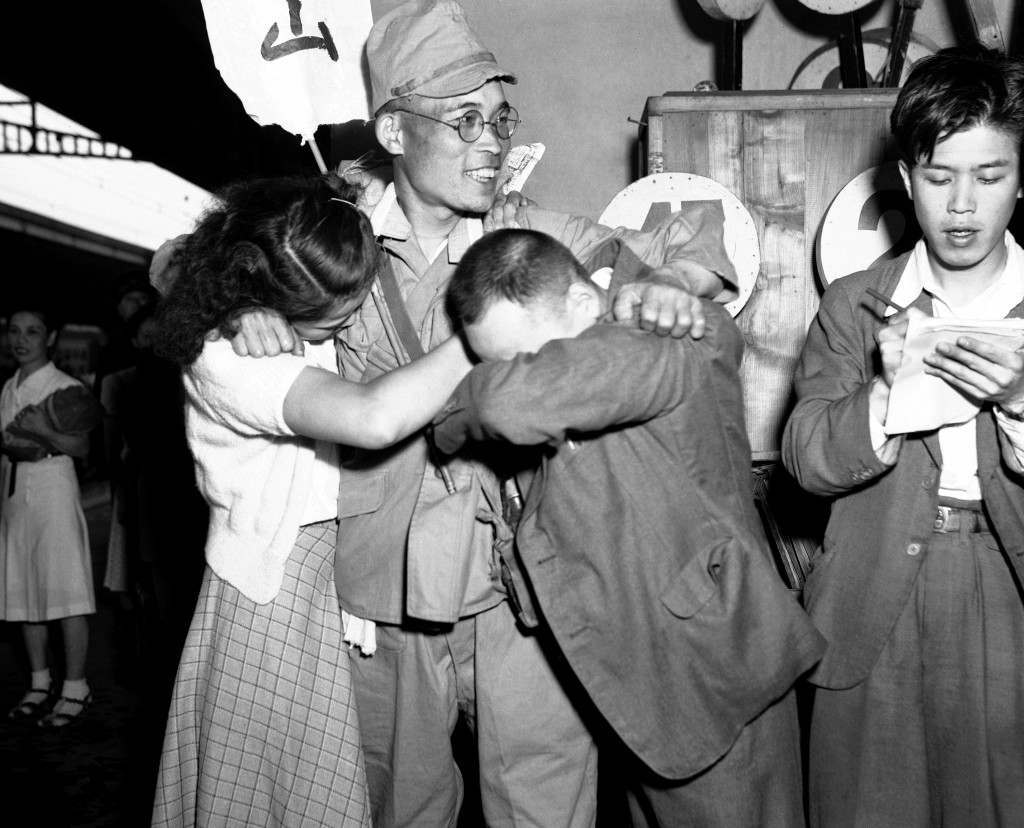 Family members greet each other as a small group of the first batch of repatriates from Russian held territory who arrived back in Japan aboard the Takasago Maru arrived at Shinagawa station a few miles from Tokyo on July 6, 1949. Their wives and children, many separated for over five years, were on hand to greet their husbands who they had thought lost in the war. (AP Photo/Charles Gorry) Ref #: PA.11317035
