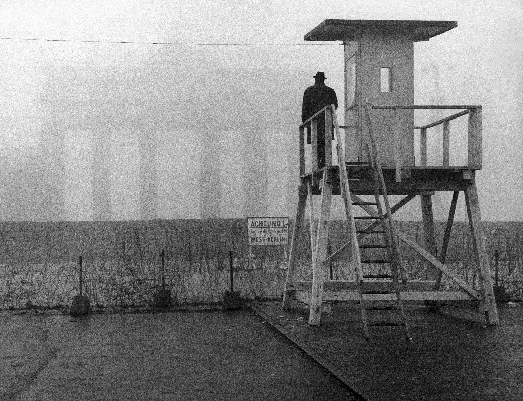 The Brandenburg Gate is shrouded in fog as a man looks from a watchtower over the Wall to the Eastern part of the divided city on November 25, 1961 in Berlin, Germany. The tower was erected by the West German police to observe the Inner-German border. (AP Photo/Heinrich Sanden Sr.) PA-11324538