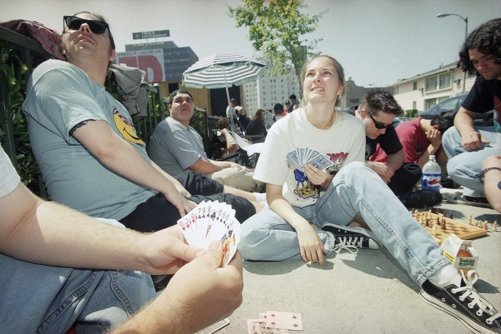 "Brian Pate of Burbank, Calif., foreground, hides his hand of cards from friends Melissa Filbeck of Sunland, Calif., and Ben Johnson of Fullerton, Calif., as they wait in line at the Mann Chinese Theatre for ""Star Wars: Episode I, The Phantom Menace"" tickets, in the Hollywood section of Los Angeles on Wednesday, May 12, 1999. The three have been waiting in line since midnight last night. (AP Photo/Chris Pizzello)"