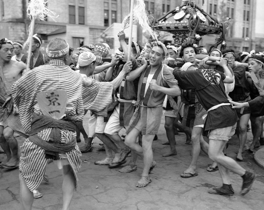 These excited young men are taking part in a festival in the Konda district of the city of Tokyo on April 7, 1949, sponsored by a small restaurant owner in the locality (who also had all the concessions cornered). They are carrying the neighborhood's shrine on their shoulders, all the time jumping up and down and chanting. (AP Photo/Charles P. Gorry) Ref #: PA.11400209