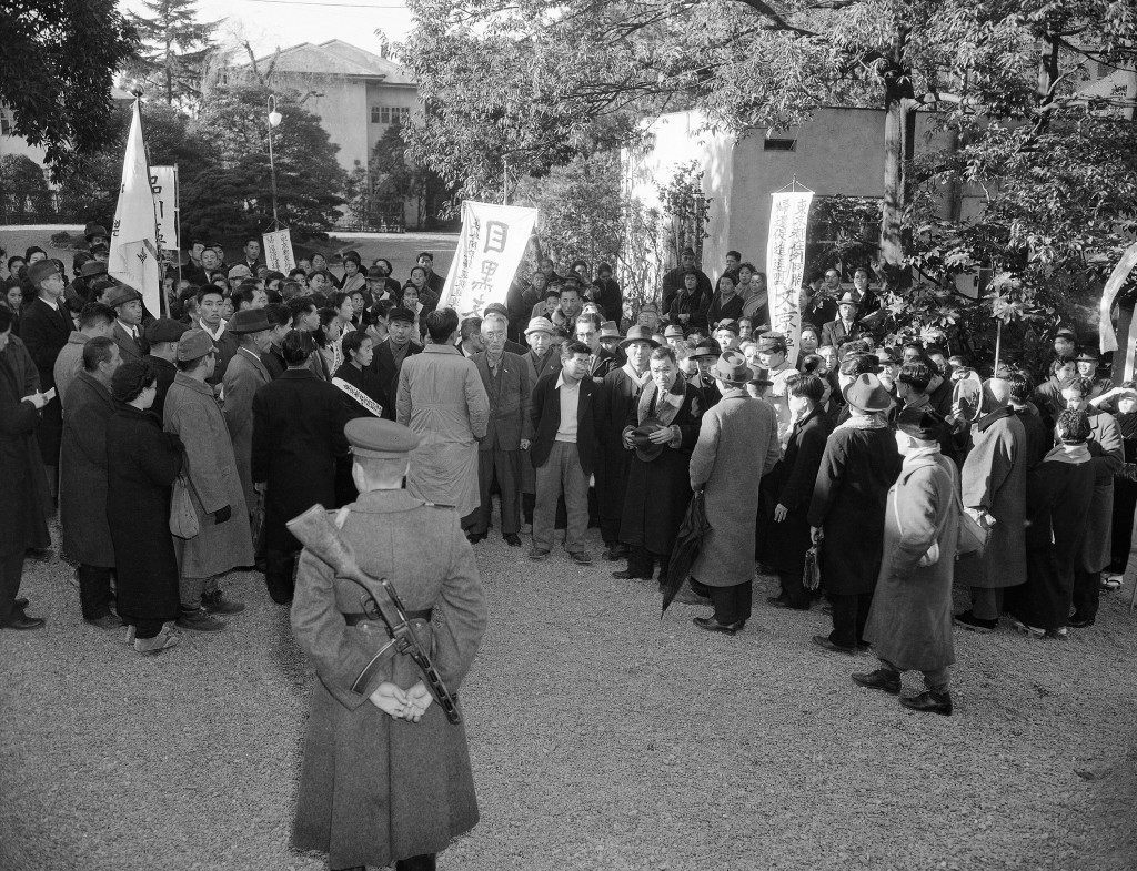 "Russian soldier with tommy gun stands guard outside the Russian Embassy as the members of the ""Repatriation Association of Japan"" await an answer to present their case to this head of the mission in person, in Tokyo, Japan on Dec. 22, 1949. (AP Photo/Charles Gorry) Ref #: PA.11447050"