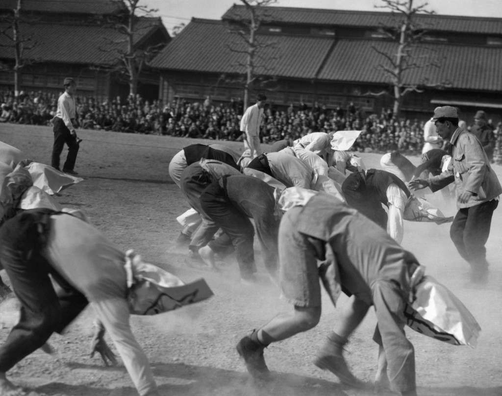 The Potato Race is underway as the contestants, employees of the Imperial household, race toward the finish line in Tokyo, Japan on April 20, 1947. Besides wearing bags to slow them, they are required to run backwards. This is an event of an annual field day on the palace grounds. (AP Photo) Ref #: PA.11460502