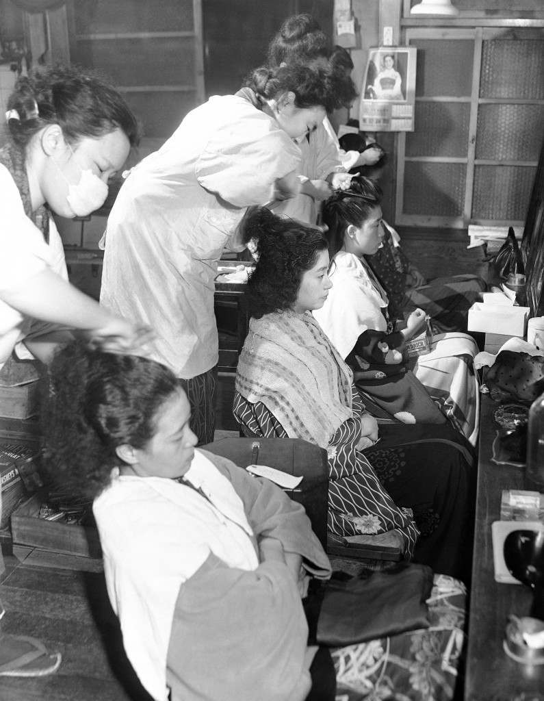 Beauty parlor in the Shmbashi district (Tokyo's number one geisha district) as the girls get ready for the New Year parties and celebrations they will attend in the evening on Jan. 4, 1950. (AP Photo/Charles Gorry) Ref #: PA.11484373