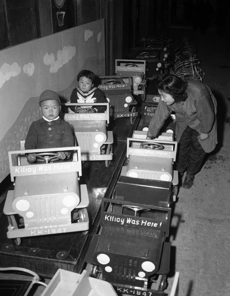 "Japanese children, visiting a Tokyo department store on March 21, 1947, try out toy jeeps bearing the slogan, ""Kilroy was here,"" placed on them by the Japanese manufacturer. (AP Photo/Charles Gorry) Ref #: PA.11484377"