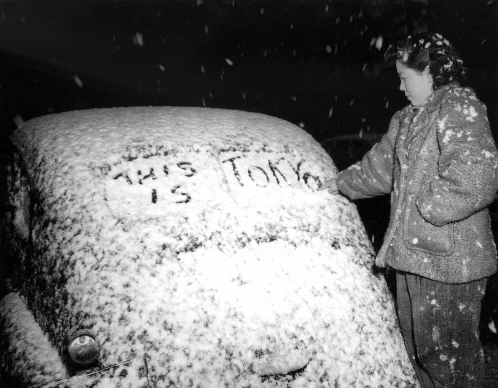 Usheeko Sato, a resident of Tokyo, Japan writes on the snow-covered rear window of an automobile in the Japanese capital on Feb. 12, 1946. (AP Photo/Charles Gorry) Ref #: PA.11497408