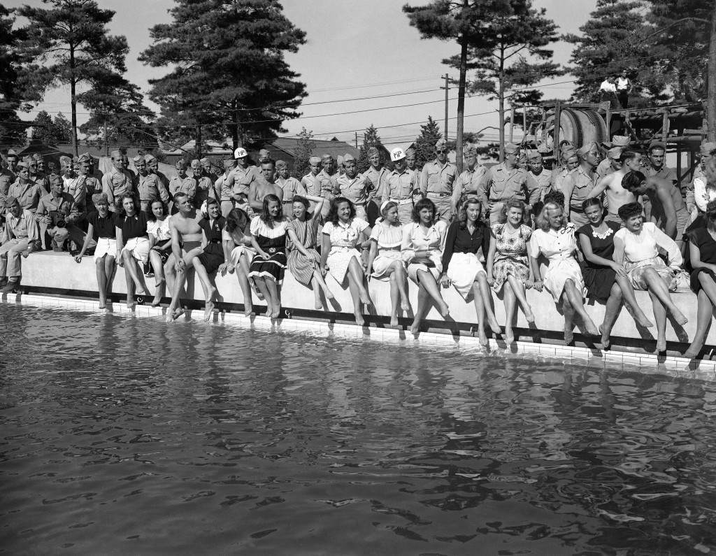 Show girls from the Mikado theater in Tokyo, their legs crossed and bare feet dangling near the water, pose on the side of a swimming pool at a new American air base at Yokota, Japan on August 17, 1946. How one male, presumably a soldier, got into the otherwise all-girl lineup at pool's edge was not explained. Uniformed soldiers stand behind the girls. (AP Photo/Charles Gorry) Ref #: PA.11560047