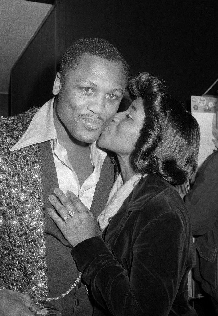 Wife Florence plants kiss on cheek of Joe Frazier, after the former heavyweight champ opened his song and dance revue at New York's Rainbow Grill on Monday, Jan. 31, 1977. The revue has been engaged for a month, and the engagement is the biggest break of Frazier's now full-time show biz career. (AP Photo/Richard Drew) Ref #: PA.11561518  Date: 31/01/1977