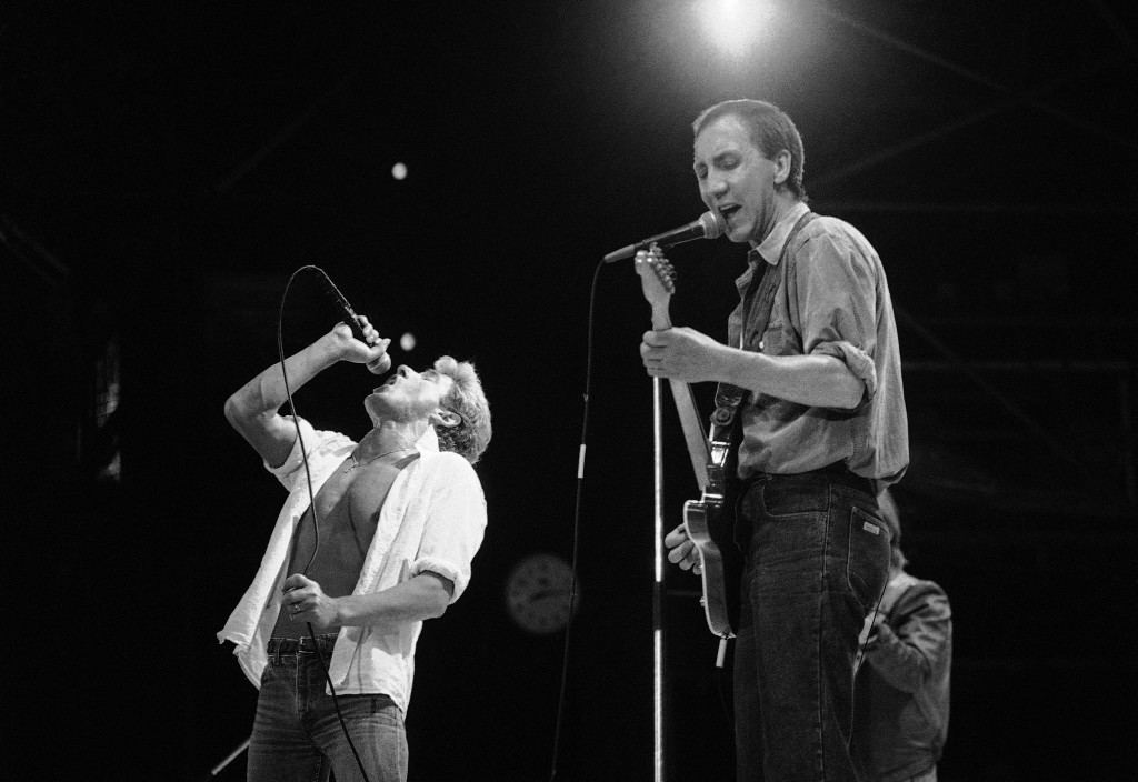The Sting, right, joins the Dire Straits group during the Live Aid famine relief concert at London's Wembley Stadium on Saturday, July 13, 1985. At left is Dire Straits lead singer Mark K. Knopflen. (AP Photo) PA-11599262