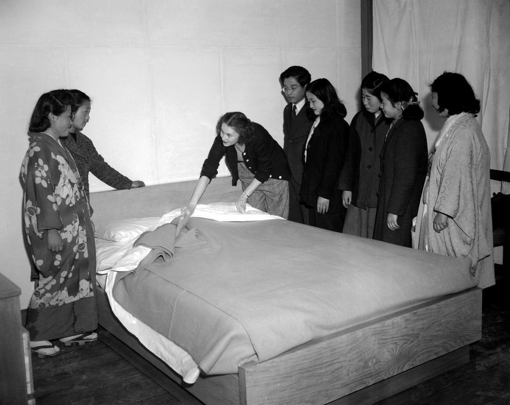 Although given preliminary instructions the girls are a bit vague about the proper making of a bed. Mrs. Anderson, with the help of an interpreter attached to the liaison section for the housing development, demonstrates the American way of bed making in Tokyo, Japan on April, 14, 1947. (AP Photo) Ref #: PA.11607761