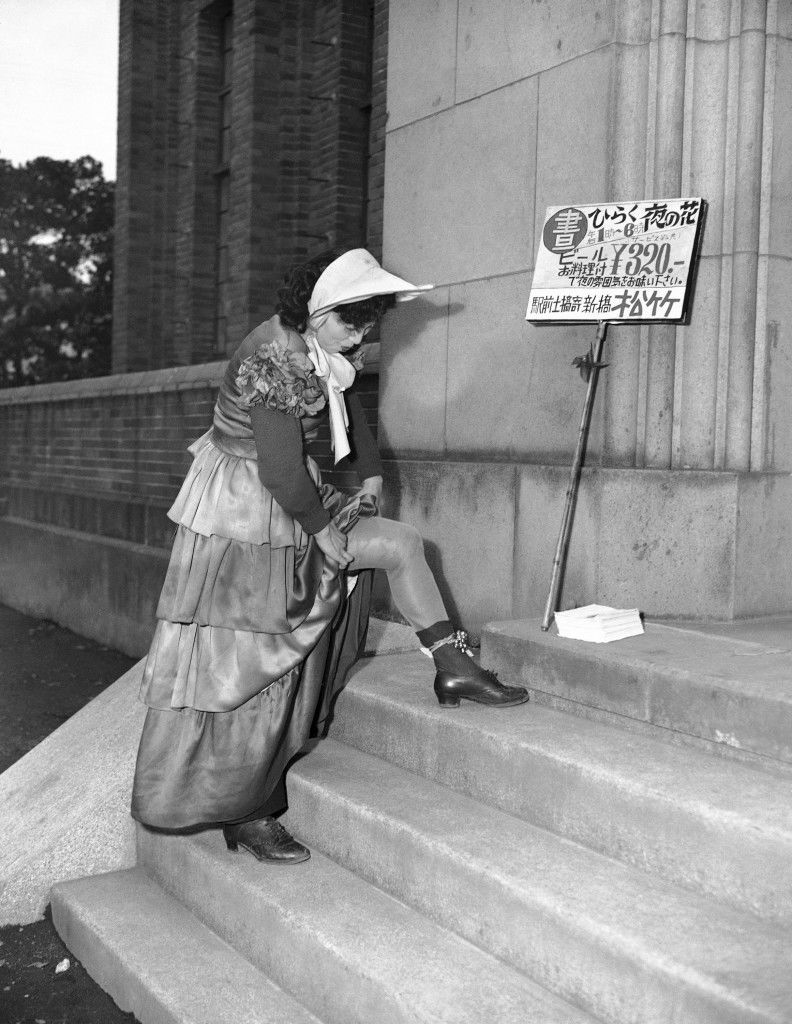 A sandwich girl who carries a sign proclaiming a new type of club where folks who work nights can come and enjoy themselves during the day, stops to adjust the bells on her ankles in Tokyo, March 19, 1950. The café hours are from 1 to 6 p.m. and Japanese beer sells for 320 yen. (AP Photo/Charles Gorry) Ref #: PA.11617163