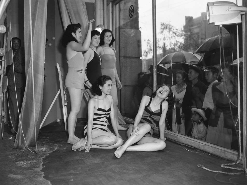 To draw the public's attention to a new line of bathing suits, a Tokyo department store uses live models to show off the suits, June 5, 1950. The rain didn't bother the curious and both the girls and the crowd seemed to like the idea of staring at each other through the glass. (AP Photo) Ref #: PA.11617196