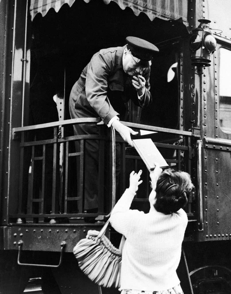 Winston Churchill, clad in siren suit and smoking a cigar, leans from a train at Quebec, Canada on August 11, 1943. To take a fan's autograph book in which to add his signature as he arrived in the Canadian city. (AP Photo) Ref #: PA.11681138  Date: 11/08/1943