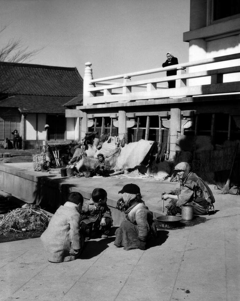 Near the railroad station a group of unfortunate Japanese squatters all bundled up in rags sit in front of their make-shift homes - some straw matting placed against the wall to break the cold wind in Tokyo on March 19, 1950. (AP Photo/Charles Gorry) Ref #: PA.11729070