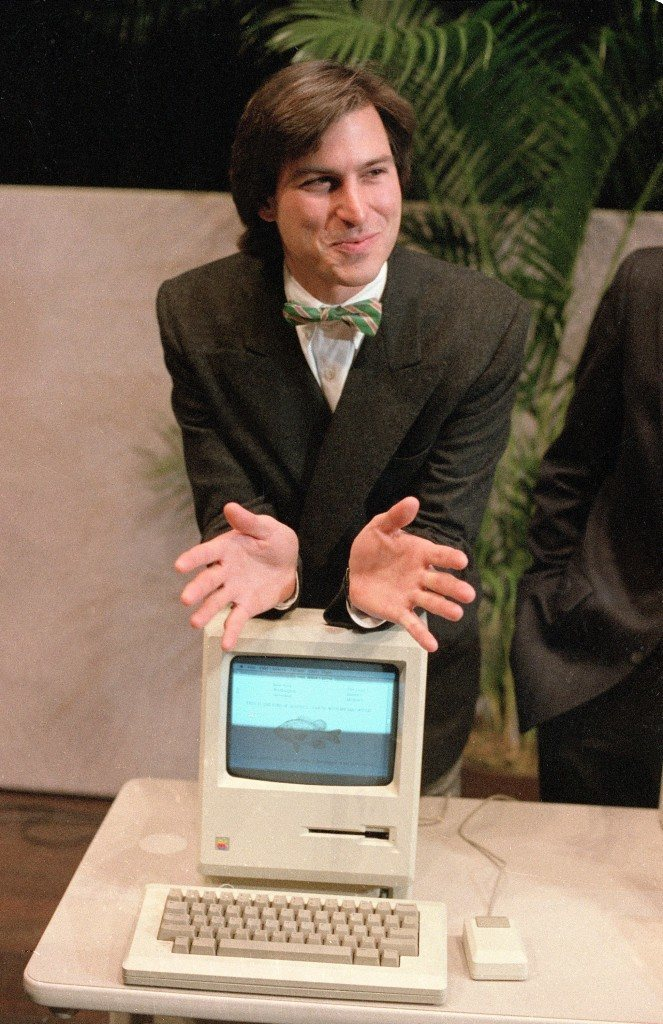 "In this Jan. 24, 1984, file photo, Steve Jobs, chairman of the board of Apple Computer, leans on the new ""Macintosh"" personal computer following a shareholder's meeting in Cupertino, Calif. Apple on Wednesday, Oct. 5, 2011 said Jobs has died. He was 56. (AP Photo/Paul Sakuma, File)"