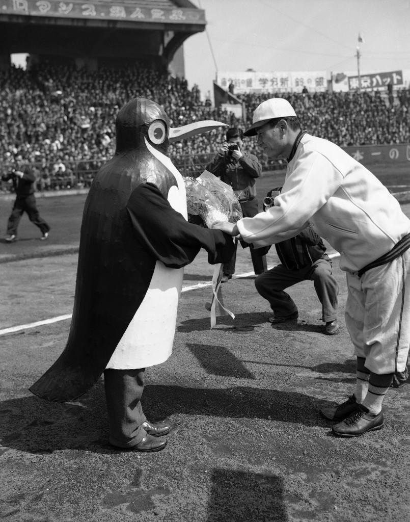 As the baseball season opened in Japan, a penguin-costumed attendant presents flowers to the manager of one of the eight teams in the league in Tokyo on March 25, 1949. Every manager gets a bouquet on opening day. (AP Photo/Charles Gorry) Ref #: PA.11880696