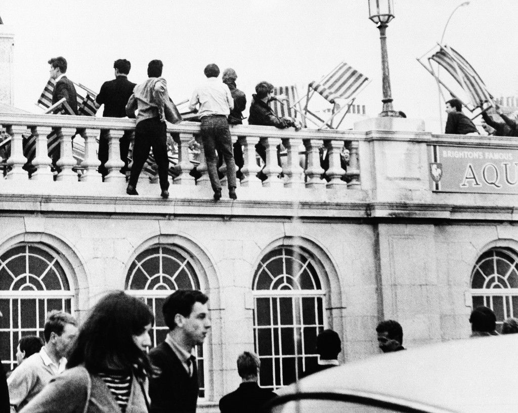 "Youths use deckchairs as weapons during a fight on May 19, 1964 on the roof of the Aquarium in Brighton, Sussex, on white Monday, May 18. Over the white weekend sea-side resorts on the south coast were the scenes of battles between rival gangs of""Mods"" and ""Rockers"" Ref #: PA.11936309  Date: 19/05/1964"
