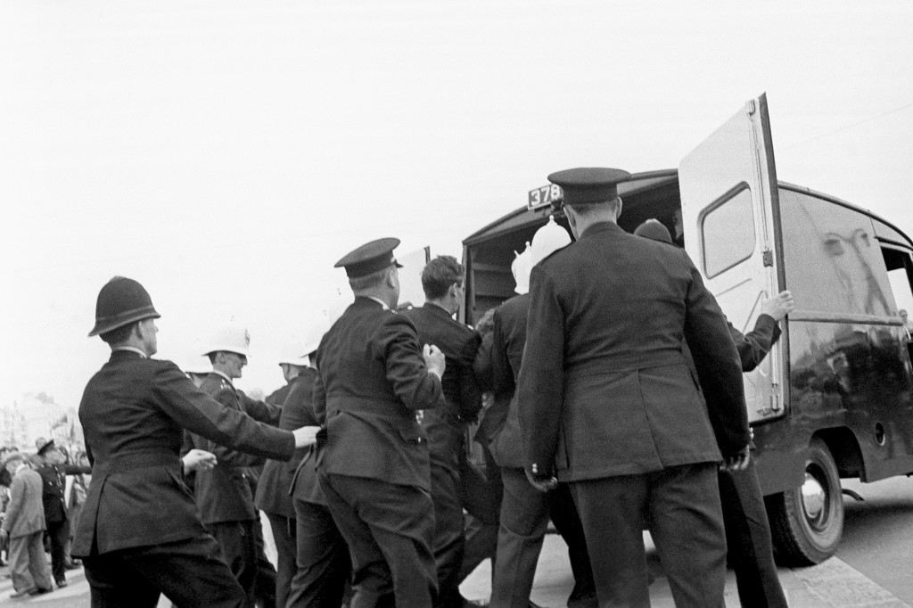 A struggling youth, surrounded by a group of policemen, is put in a van at Brighton where mods and rockers clashed on the promenade Ref #: PA.11941463  Date: 18/05/1964