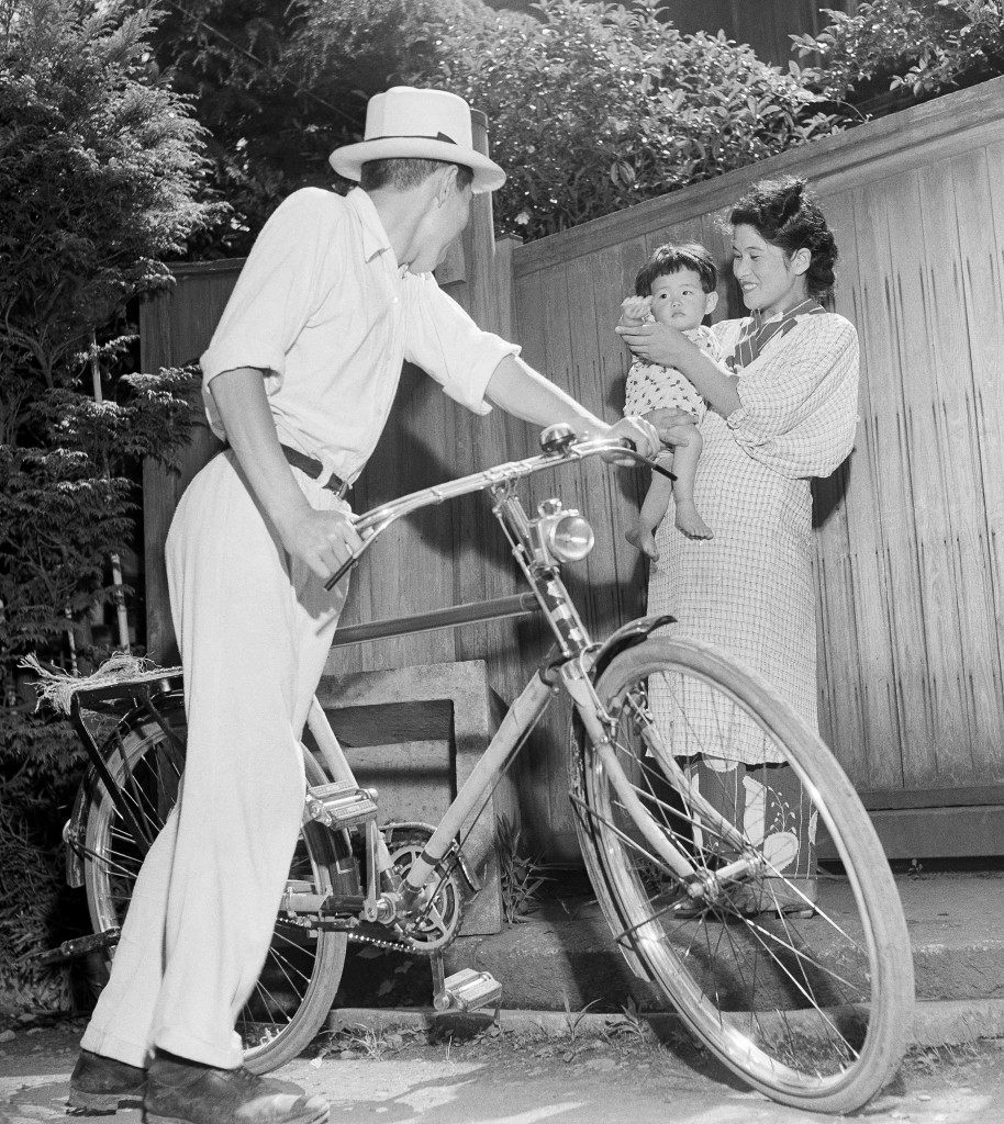 Baby Misuko, held by her mother Umeko, waves goodbye to papa-san as he goes to work on his bicycle, from their home in Tokyo, July 30, 1948. The old bicycle carries Tomosaburo Kawanabe six miles to his bookstore in downtown Tokyo. He makes a comfortable living even at inflated prices. (AP Photo) Ref #: PA.12003583