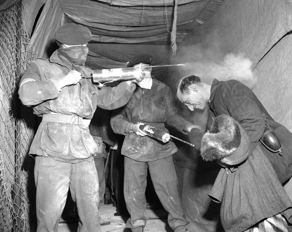 A Jewish refugee bows low on Feb. 16, 1947, as he receives a charge of DDT disinfectant from soldiers of the British 6th Airborne Division before leaving Jerusalem on the Cyprus-bound ship, Ocean Vigour. (AP Photo/J. Walter Green) Ref #: PA.12465873 Date: 16/02/1947