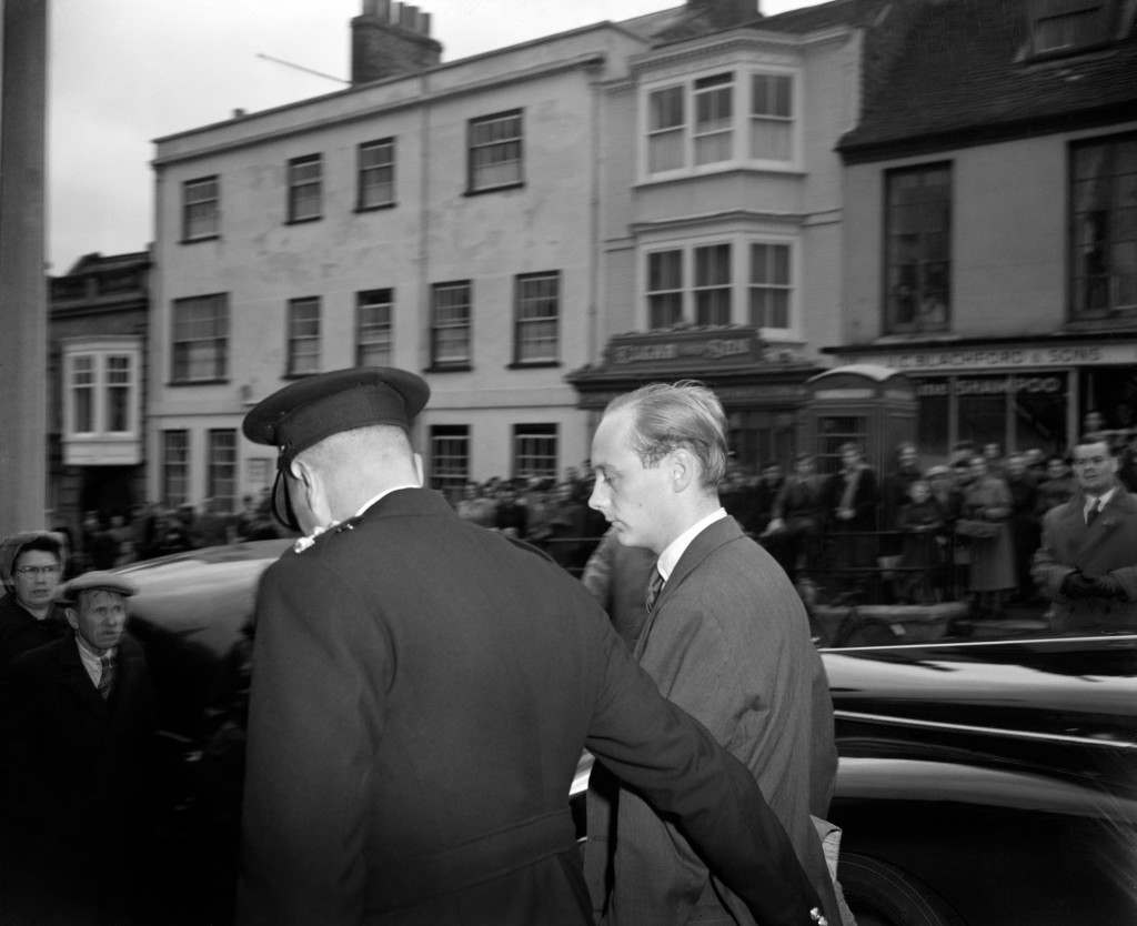 "Chief Inspector L.C Orchard leads Lord Montagu into Lymington Town Hall Court. He is charged with ""conspiracy to incite certain male persons to commit serious offences with male persons"". Lord Montagu, former director of a London publicity firm, had returned to England only a few hours earlier from France. Ref #: PA.12517618  Date: 08/11/1953"