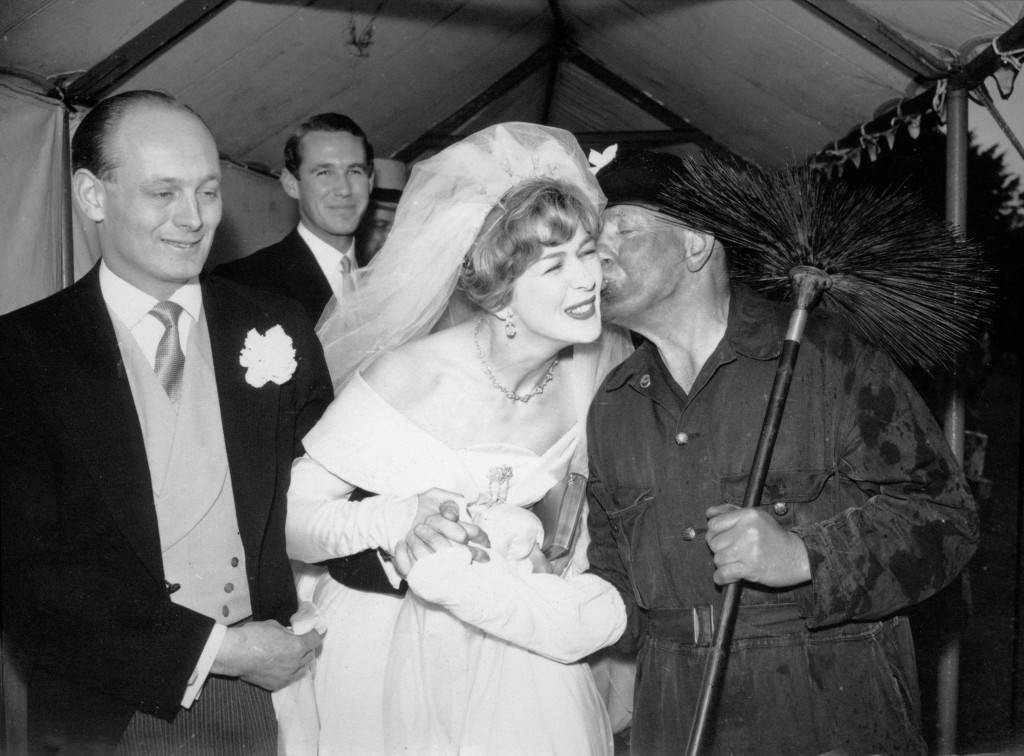 Lord Montagu watches with a smile as his bride, the former Miss Belinda Crossley, gets a good-luck kiss from chimney sweep Frank Miles as she leaves the 13th century Abbey Church at Beaulieu, Hampshire, after their wedding. Ref #: PA.12527525  Date: 11/04/1959