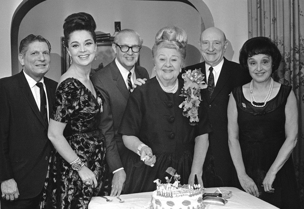 "Sophie Tucker, the ""Last of the Red Hot Mamas"""", cuts a birthday cake at a famous French Quarter Restaurant in New Orleans, La., Jan. 14, 1964. The party was given in honor of her 80th birthday. On her right is Ted Shapiro, musical director, that has been with her for 43 years. On her other hand is Seymour Weiss, president, and general manager of a large New Orleans hotel. Others are unidentified. Yhe cake says 'KEEP BREATHING' (AP Photo/VTK) Ref #: PA.12587694"