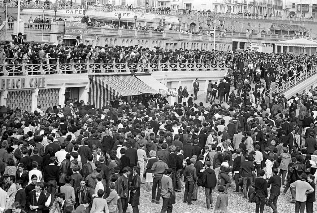 Police take away a youth when a large crowd of mods gathered on the beach in Brighton, as holidaymakers watch the scene from the promenade. It was a scene repeated a number of times at the Sussex resort, where gangs of mods and rockers clashed. * ...during Bank Holiday periods. Ref #: PA.1309167  Date: 18/05/1964