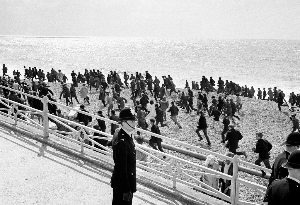Police officers watch a large crowd of mods running along the beach in Brighton, a scene repeated a number of times at the Sussex resort, where gangs of mods and rockers clashed during Bank Holiday periods. Ref #: PA.1309168  Date: 17/04/1965