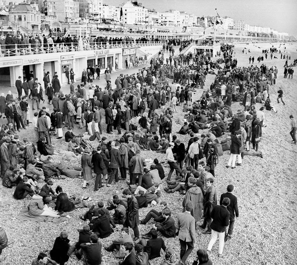 The Mods and Rockers bank holiday riots in Brighton. A large crowd of mods gathered near the Palace Pier on the beach in Brighton, a scene repeated a number of times at the Sussex resort, where gangs of mods and rockers clashed during Bank Holiday periods. Ref #: PA.1309169  Date: 17/05/1964
