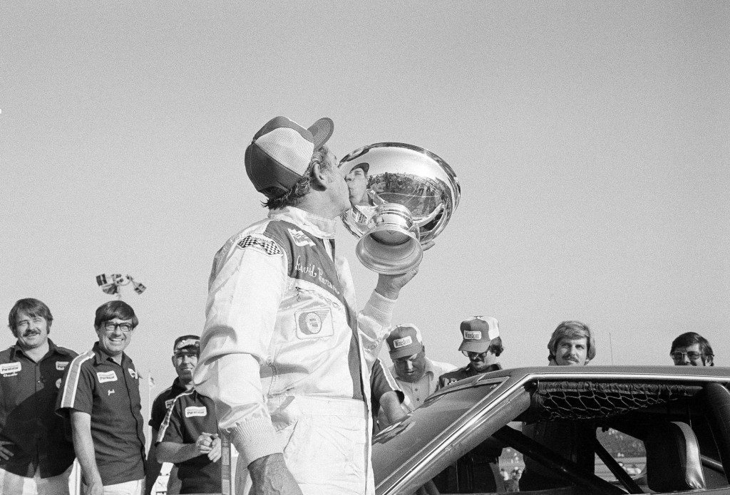 David Pearson plants a kiss on the trophy he received for winning the Los Angeles Times 500 stock car race at the Ontario Motor Speedway at Ontario, Calif., Nov. 22, 1976. Pearson collected about $18,500 for his tenth victory this season. The race is the season finale of NASCAR Grant National stock car racing. (AP Photo/George Brich) Ref #: PA.13477523  Date: 22/11/1976