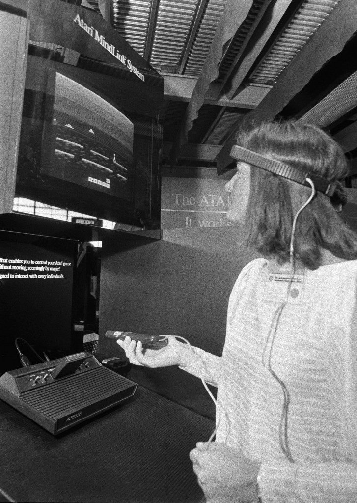 In this June 5, 1984, file photo, a woman in Chicago demonstrates Atari's new game, Mind Link, which utilizes a headband that picks up electrical impulse from the movement of the forehead and transmits them to a receiver attached to a video game or home computer console. (AP Photo/Charlie Knoblock)