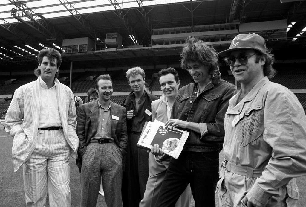 BAND AID 1985: Rock stars at Wembley stadium, London, following the announcement that Band Aid is to stage the biggest rock event the world has ever seen to raise millions for the Ethiopian famine appeal. (l-r) Tony Hadley, Midge Ure, Gary Kemp, Adam Ant, Bob Geldof and Elton John.  *19/12/01:  Rock stars at Wembley stadium, London, following the announcement that Band Aid is to stage the biggest rock event the world has ever seen to raise millions for the Ethiopian famine appeal. (l-r) Tony Hadley, Midge Ure, Gary Kemp, Adam Ant, Bob Geldof and Elton John.  It was announced that Wembley would be the site for the new national stadium. PA-1438356