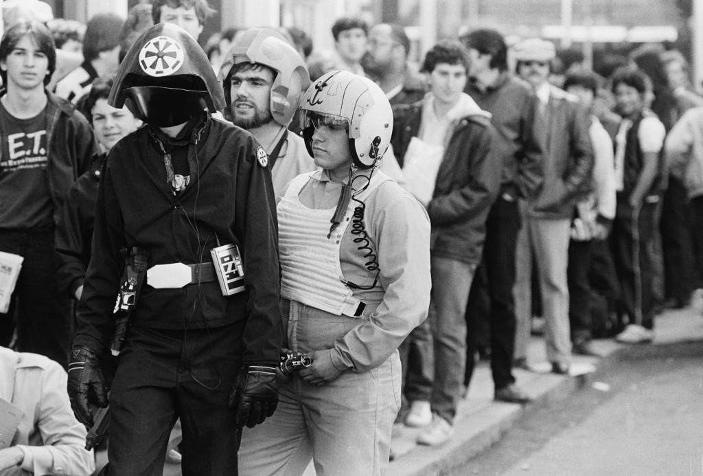 "Three costumed fans of the ""Star Wars"" movie trilogy stands in a line of ticket buyers outside a Boston Theatre Wednesday May 25, 1983, before the first Boston performance of the film ""Return of the Jedi."" From left are Kevin Maguire, as an Imperial Fire Control Officer; Stephen Robards, centre, and his brother John Robards as Rebel Fighter Pilots. (AP Photo/Southwick)"