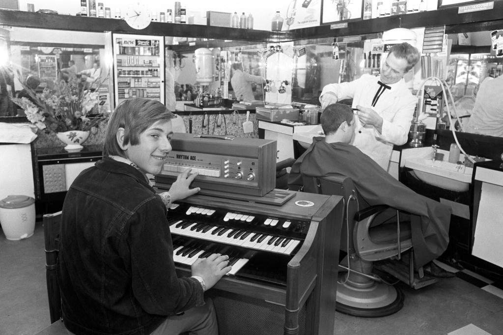 A customer plays an electric organ as he waits for his turn in the barber's chair at Clif Reynold's hairdressing salon in Withington, Manchester. Archive-PA147118-1 Ref #: PA.15216916 Date: 01/09/1970