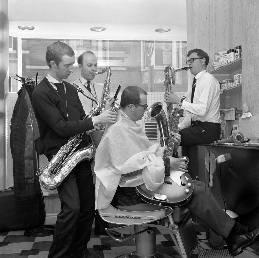 Barber Fred Walker, 21, clips a customer's hair to saxophone accompaniment at his salon in Dean Road, Scarborough. The jazz fan often attracts professional musicians to his shop and spends time practising on his tenor sax when trade is slow. Directly behind him is his music tutor Alan Walker (no relation). Archive-PA128793-1 Ref #: PA.15216957  Date: 06/07/1967