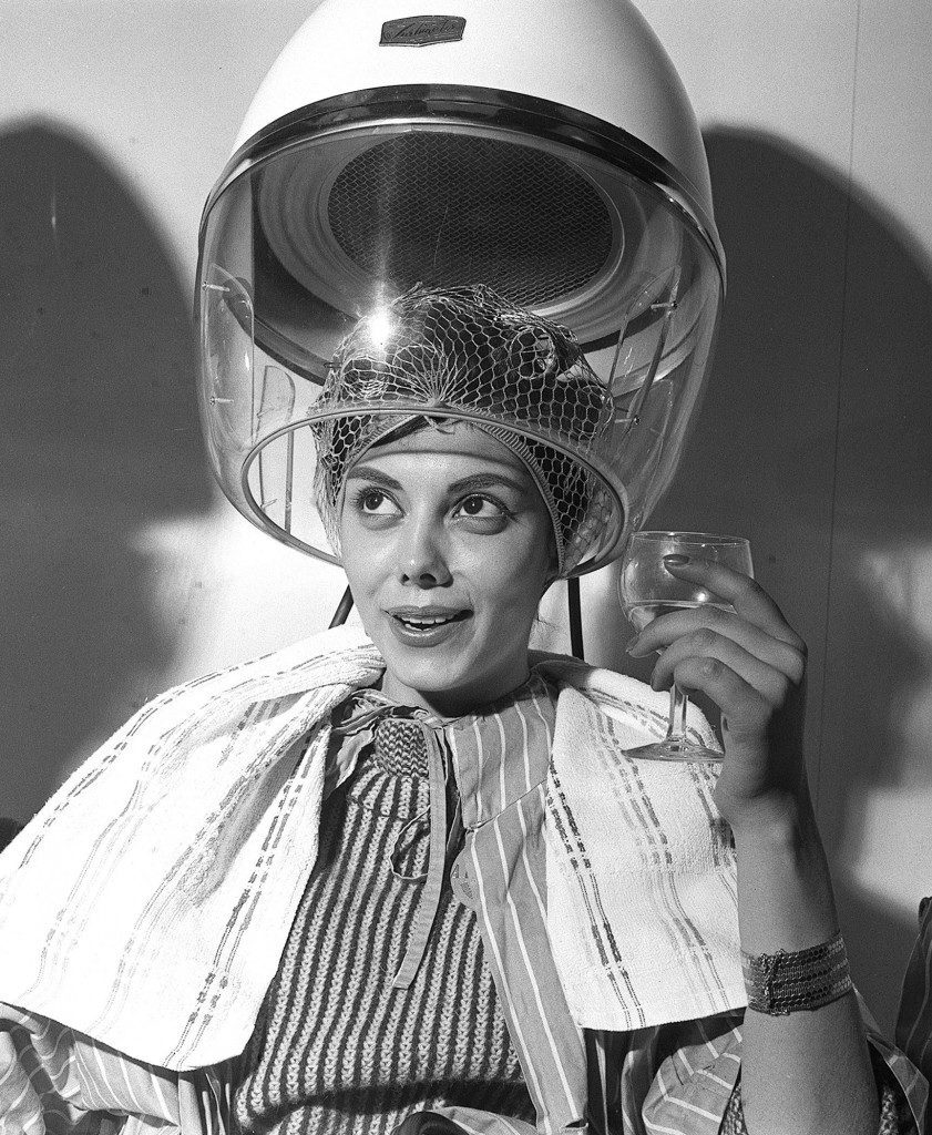Miss Norma Cappagli (Miss Argentina) pictured as she enjoyed a drink beneath the hair-dryer in a London salon when she received her hairstyle for the Miss World contest. Picture date: 7 Nov, 1960. Ref #: PA.1551828
