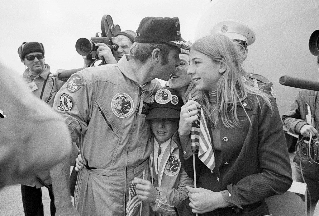 Apollo 17 command module pilot, Ronald E. Evans, is greeted by his family after the crew landed at Ellington Air Force Base, Houston, Texas, Dec. 21, 1972. Evans is sown kissing his wife, Jan, as daughter, Jaime, 13, waits her turn to kiss her dad. Son Jon, 11, is squeezed in by the trio. Evans, a commander in the U.S. Navy when he left for the moon, was promoted to captain on his return to earth. (AP Photo) Ref #: PA.15718094  Date: 21/12/1972