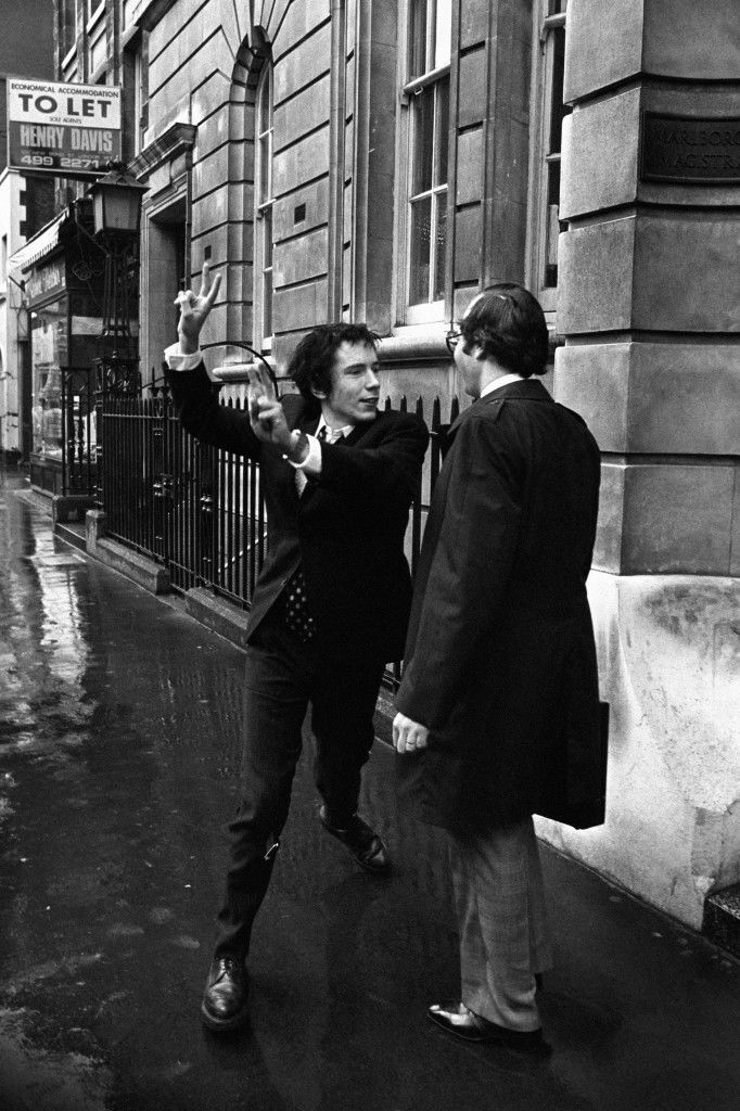 Johnny Rotten, lead singer with the Sex Pistols, giving a double V-sign to journalists after he had been fined £40 on a drugs charge at Marlborough Street Magistrates Court, London. Ref #: PA.1584042  Date: 11/03/1977