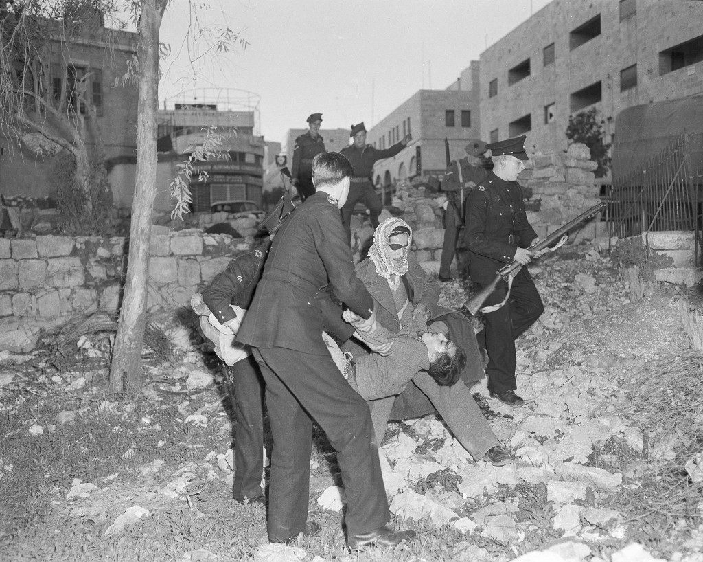 A dying Jewish raider is carried by a policeman and an Arab from a Muslim cemetery in Mamillah Road, Jerusalem, after armored car in which he and four other Jews had ridden in their bomb attack at Jaffa Gate crashed into the wall of the cemetery, Jan. 7, 1948. The car was wrecked by rifle fire from police and soldiers after dropping a second bomb at Mamillah Road. Eighteen people, mostly Arabs, were killed in the attack. (AP Photo) Ref #: PA.16054887 Date: 07/01/1948