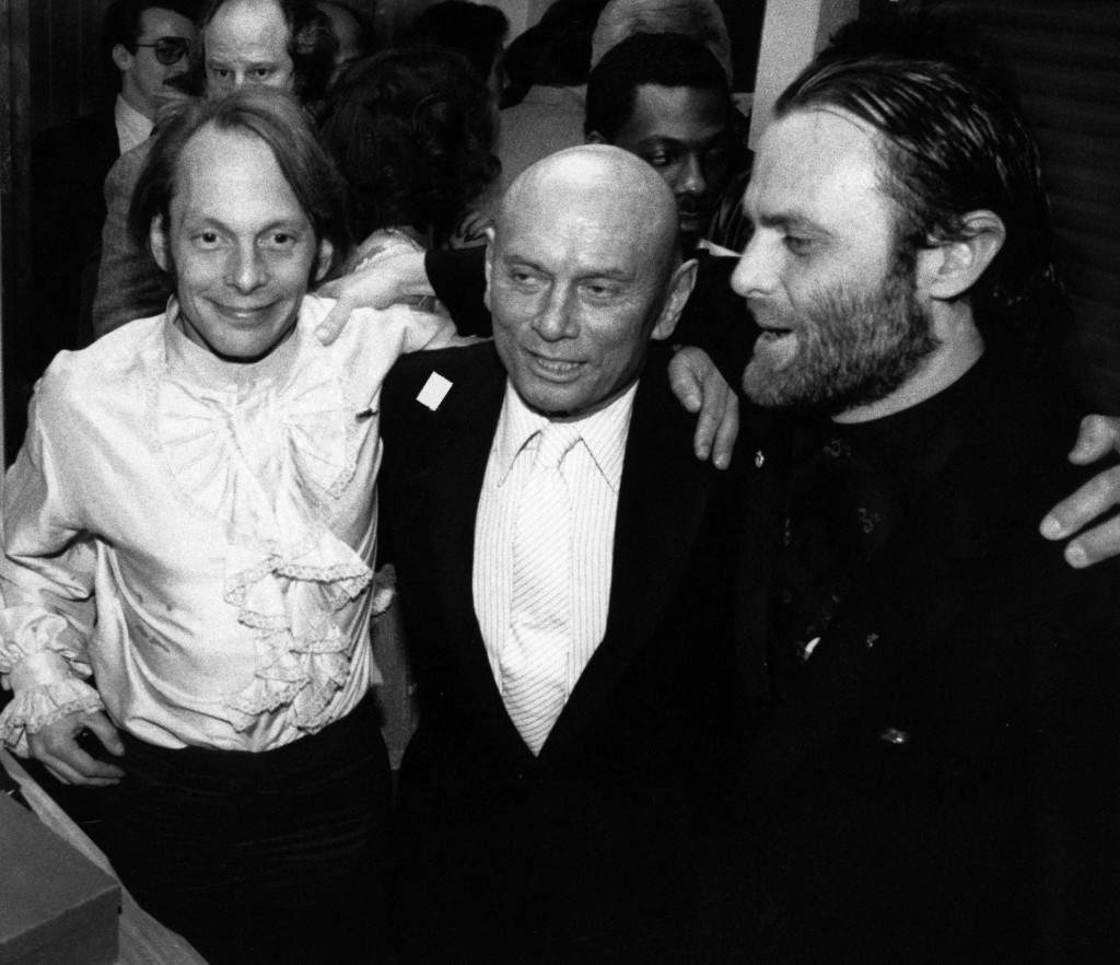 Actor Yul Brynner, center, poses with son, Rock, Left and Isaac Tigrett at the opening of the Hard Rock Cafe in New York, March 13, 1984. Tigrett and actor Dan Aykroyd are co-owners. Rock Brynner is the night manager. (AP Photo/Mitchell Tapper) Ref #: PA.16420491  Date: 13/03/1984