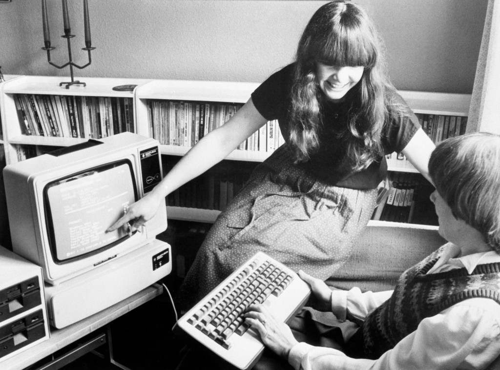 Sandy Aldrich and her daughter Philippa consult their home 'Teleputer' in Colgate. Sandy's husband Mike Aldrich is head of Rediffusion Computers in Crawley, and the Teleputer is claimed to be the first-ever product which combines the personal computer with television and videotex. Ref #: PA.18358004  Date: 27/08/1983