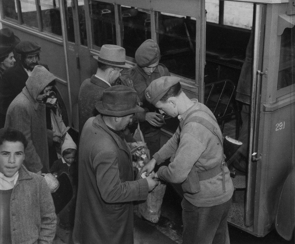 Members of the Royal Irish Fusiliers go through personal belongings and identification papers as passengers of a bus halted, Feb. 2, 1947 at a road block on the main highway between Jerusalem and Tel Aviv. (AP Photo) Ref #: PA.18363261 Date: 02/02/1947