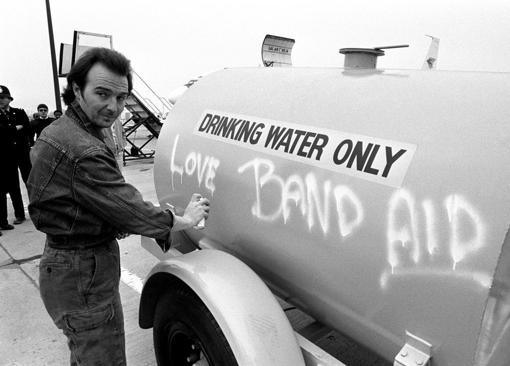 Midge Ure, 31 of the Rock Group Ultravox, who with Bob Geldof wrote the Band Aid single 'Do They Know It's Christmas?', spraying a message on a water tanker at Gatwick Airport. PA-2099466